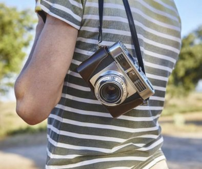 Traveler with vintage camera in the countryside. Travel background. Lifestyle